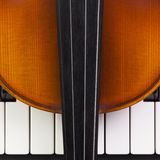 Old violin lying on the piano Stock Photo