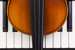 Old violin lying on the piano Stock Images