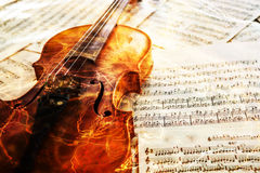 Old violin lying on the sheet of music Stock Photos