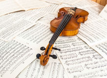 Old violin lying on the sheet of music Stock Photography
