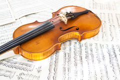Old violin lying on the sheet of music Stock Photo