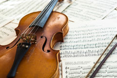 Old violin lying on the sheet of music Royalty Free Stock Image