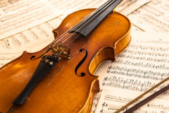 Old violin lying on the sheet of music Stock Image