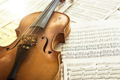 Old violin lying on the sheet of music Stock Images