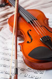 Old violin lying on the sheet of music, music concept Royalty Free Stock Image