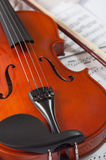 Old violin lying on the sheet of music, music concept Stock Photo