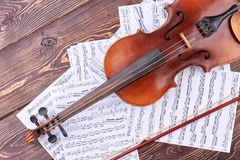 Old violin and musical notes. Vintage violin, bow and music sheets on brown wooden background. Classical stringed instrument stock images