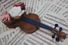 Old violin with musical notes and rose Royalty Free Stock Photos