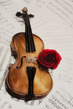 Old violin with musical notes and rose Stock Photography
