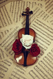 Old violin with musical notes and roses Royalty Free Stock Image