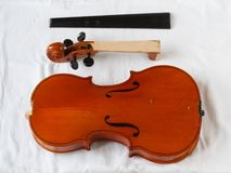 Old violin restoration: detached fingerboard and body with head royalty free stock photography
