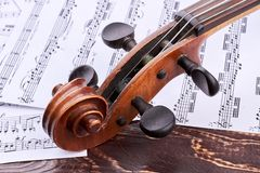 Old violin scroll and peg box. The head of intage violin on music notes background. Construction of antique violin instrument royalty free stock photos
