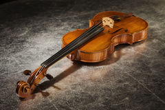 Old violin on a silver fabric Royalty Free Stock Image