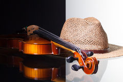 Old violin and straw hat  on black and white background. And glass desk Royalty Free Stock Photography