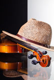 Old violin and straw hat isolated on black and white background. And glass desk Stock Photos