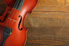 Old violin. Violin on wooden brown background closeup Stock Image