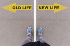 Old vs new life text arrows on asphalt ground, feet and shoes on. Old life vs New life text on yellow arrows on asphalt ground, feet and shoes on floor, personal stock photos