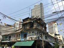 Old vs New in Silom. Old houses in front of the centre point Hotel in Silom Bangkok Thailand royalty free stock photography