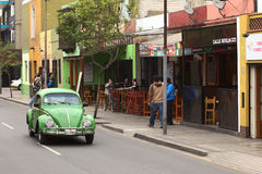 Old VW Beetle on Calle Berlin in Lima, Peru. LIMA, PERU - SEPTEMBER 22, 2011: An old green VW Beetle on the street Calle Berlin on September 22, 2011 in the Stock Photos