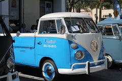 Old VW microbus parked. Old light blue Volkswagen Microbus combi or utility vehicle parked outside among other classic cars on a sunny Miami day royalty free stock images