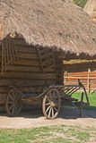Old  wagon. Old wooden wagon standing under the thatched roof Royalty Free Stock Photos