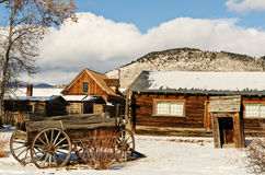 Old Wagon and Ghost Town Buildings. Old wagon sits among buildings in a Montana ghost town in the winter Stock Images