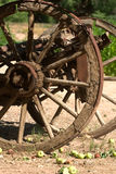 Old wagon wheel with apples. Partial view of an old rusty wagon wheel, with apples in the foreground Stock Photo