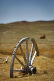 Old wagon wheel in countryside. Old broken wagon wheel embedded ground, Bodie State Park, California, U.S.A Royalty Free Stock Photography