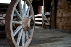 Old, wagon wheel. An old vintage wagon wheel, close-up view. The rim is made of rusted metal Royalty Free Stock Image
