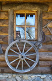 Old wagon wheel on wall. Of the building with window Stock Photography