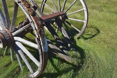 Old wood wagon wheels. Old wagon wheel with wood hub and spokes located in a meadow Royalty Free Stock Image