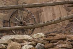 Old wagon wheel. An old wagon wheel by an old wooden fence Stock Image