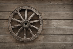 Old wagon wheel on wooden wall Stock Photos