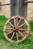 Old wagon wheel. The old wagon wheel in the yard of a village house. Texture, background Stock Photography
