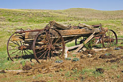 Old wooden wagon in Wyoming hills. Wooden and iron spoke wagons are stored in farmers fields and pastures in Wyoming Stock Photo