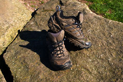 Old walking shoes. Old muddy walking shoes on rocks Stock Photo