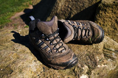 Old walking shoes. Old muddy walking shoes on rocks Royalty Free Stock Photo