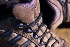 Old walking shoes. Old muddy walking shoes on rocks Stock Photography