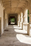 Old walkway. Old pillar lined walkway adjacent to formal gardens in Stock Photo