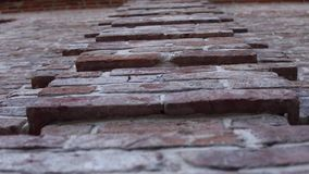 Old wall with ancient brickwork, brick background. Old wall with ancient crumbling brickwork, you can see the structure of the bricks. The camera is directed stock video