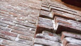 Old wall with ancient brickwork, brick background. Old wall with ancient crumbling brickwork, you can see the structure of the bricks. The camera is directed stock video footage