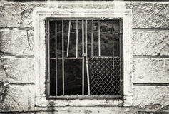 Old wall with barred window, black and white. Old wall with barred window. House for demolition. Architectural element. Black and white photo Royalty Free Stock Images