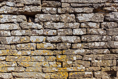 Old wall built of stones. And covered with lichens Royalty Free Stock Photo