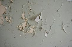 Old wall with chipped paint. Old wall: chipped, partially peeled-off white, beige and green paint royalty free stock photography