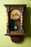 Old wall clock. Old vintage clock hanging on green wall Stock Photo