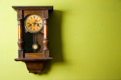 Old wall clock. Old vintage clock hanging on green wall Stock Photography