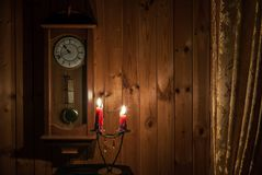 Old wall clock and candles. Old wall clock on a wooden wall and burning candles Stock Image