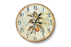 Old wall clock with fading and rust against the white bleached walls. The dial of the watch with a collage of plants. Old wall clock with fading and rust stock photography