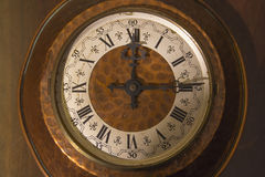 Old wall clock with roman numerals. Old copper clock with roman numerals. Vintage, retro, antique Stock Image