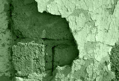 Old wall with the damagedplaster. Structure of an old wall, in color, slag stone, plaster, a shade green, for a background Royalty Free Stock Photo